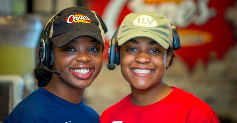 A close up of two Raising Cane's workers smiling at the camera while wearing drive-through headsets