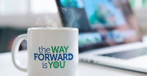 """A steaming hot mug sitting on a table with the mug having the text """"the WAY FORWARD is YOU"""""""